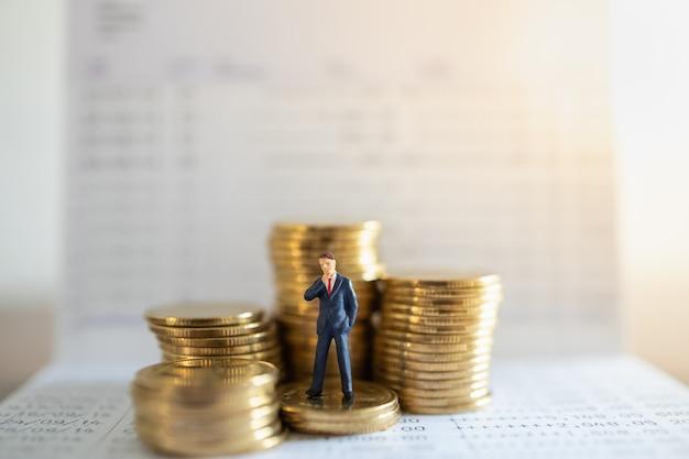 Biznes, pieniądze inwestycje i planowanie concept.biznesmen miniaturowa postać osób stojących na stosie złotych monet z książeczką bankową.