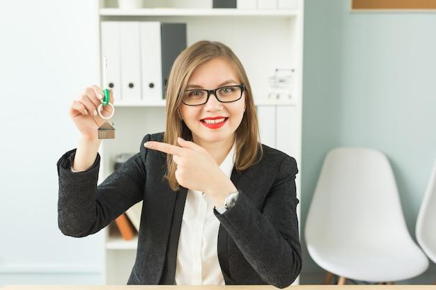Biznes, pośrednik w handlu nieruchomościami i koncepcja nieruchomości - portret atrakcyjnej uśmiechniętej kobiety trzymającej klucze