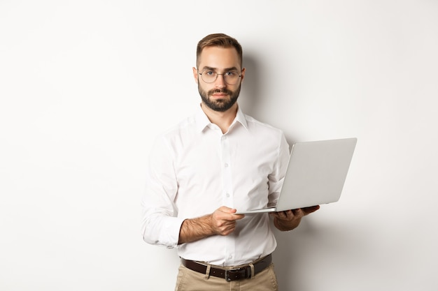Biznes. przystojny menedżer pracuje na laptopie, trzymając komputer i patrząc na kamery, na stojąco
