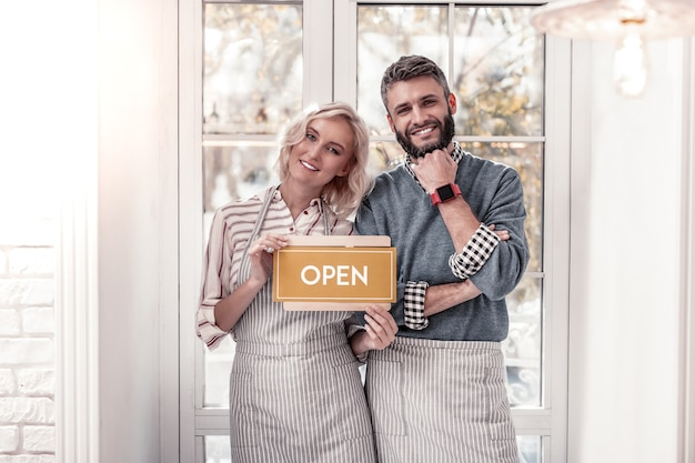 Biznes rodzinny. zachwycona wesoła para uśmiecha się do ciebie otwierając własną kawiarnię