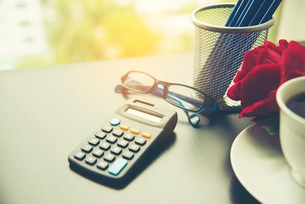 Biznes rzeczy z ołówkiem, kalkulator, czerwona róża, filiżanka kawy, zestaw papeterii.