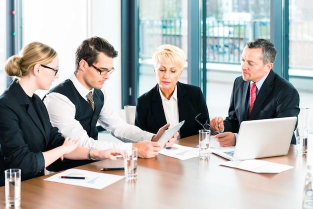 Biznes - spotkanie w biurze, biznesmeni lub prawnicy w zespole omawiają dokument na komputerze przenośnym