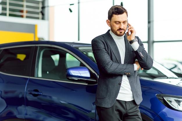 Biznes, sprzedaż samochodów, konsumpcjonizm i koncepcja ludzi - szczęśliwy człowiek na tle salonu samochodowego lub salonu