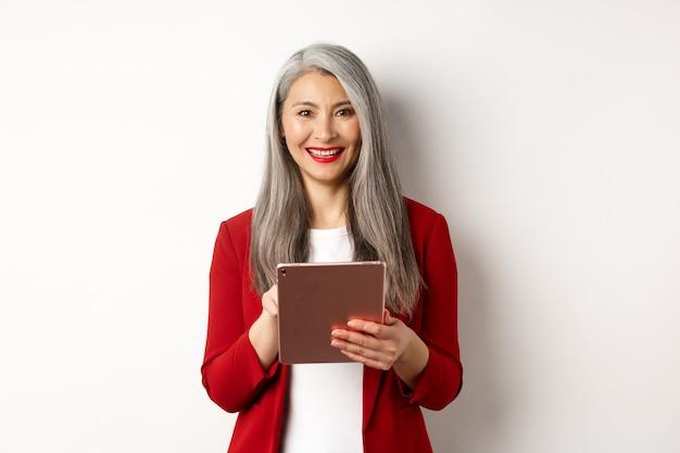 Biznes. starszy przedsiębiorca kobieta pracuje na cyfrowym tablecie i uśmiecha się szczęśliwy w aparacie, ubrany w czerwoną marynarkę i makijaż, stojąc na białym tle.