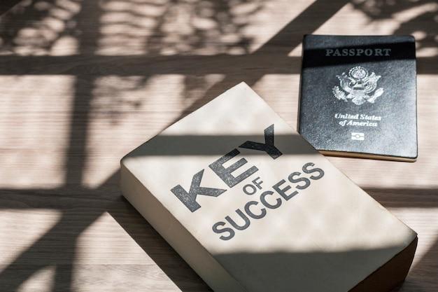 Biznes sukces książka i paszport blisko okno w ranku.