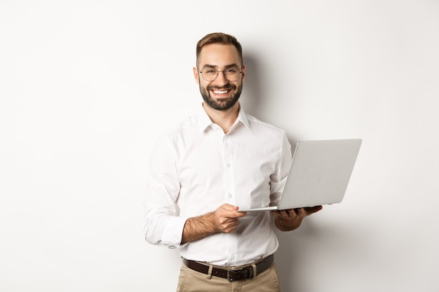 Biznes. sukcesy biznesmen pracy z laptopem, przy użyciu komputera i uśmiechnięty, na stojąco