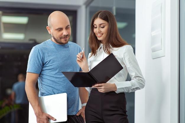 Biznes, szczęśliwy, pracownik i sekretarz stojący w biurze z laptopem i dokumentami.