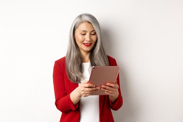 Biznes. udany starszy bizneswoman pracuje z cyfrowym tabletem, czytając ekran i uśmiechając się, stojąc w eleganckiej czerwonej marynarce na białym tle.