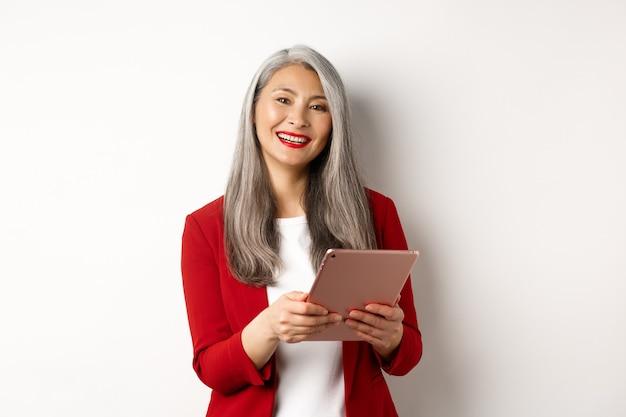 Biznes. udany starszy bizneswoman pracuje z cyfrowym tabletem i uśmiechnięty, stojący w czerwonej marynarce na białym tle.