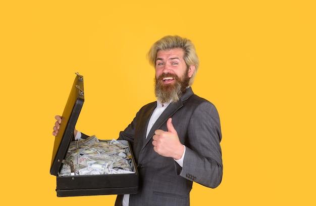 Biznes uśmiechnięty biznesmen trzymaj walizkę z pieniędzmi banknoty dolarowe rachunki dyrektor generalny brodaty biznesmen in