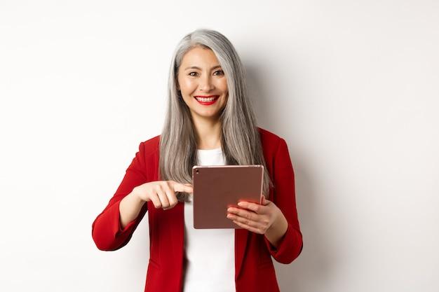 Biznes. uśmiechnięty starszy bizneswoman za pomocą cyfrowego tabletu, wskazując palcem na ekranie, stojąc na białym tle.