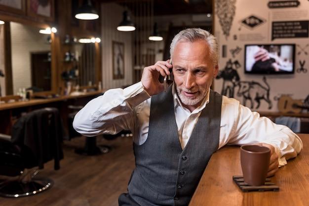 Biznes w przerwie kawowej. portret atrakcyjny starszy biznesmen siedzia? przy barze i po mobilnej rozmowie.
