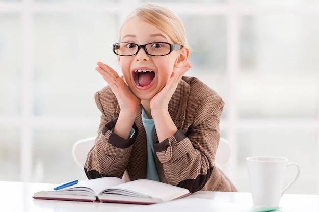 Biznes w zabawie. wesoła dziewczynka w okularach i formalnym stroju siedzi przy stole i krzywi się