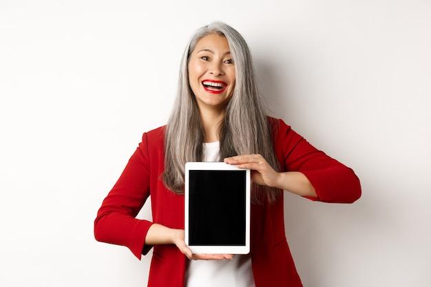 Biznes. wesoła azjatycka bizneswoman w czerwonej marynarce, pokazująca cyfrowy ekran tabletu i uśmiechnięta, wprowadza aplikację lub promocję, białe tło.