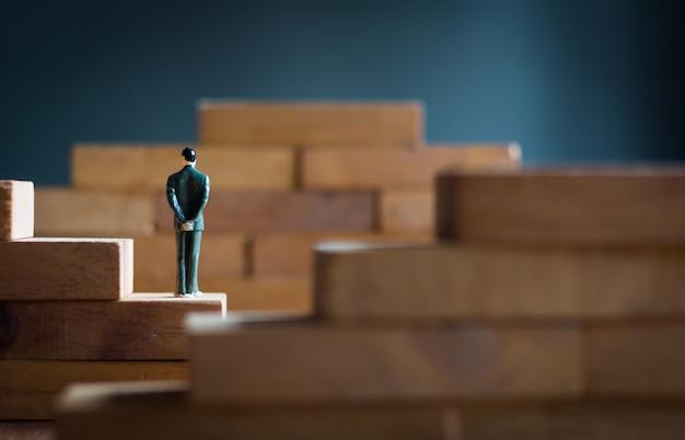 Biznes, zarządzanie, koncepcja strategii. biznesmen postać ręce splecione z tyłu stoją na drewnianej drabinie bloku