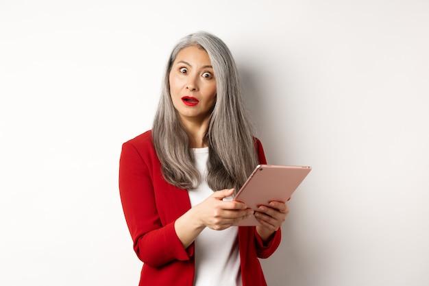 Biznes. zaskoczony bizneswoman azjatyckiego, patrząc pod wrażeniem po przeczytaniu czegoś na cyfrowym tablecie, stojąc na białym tle.