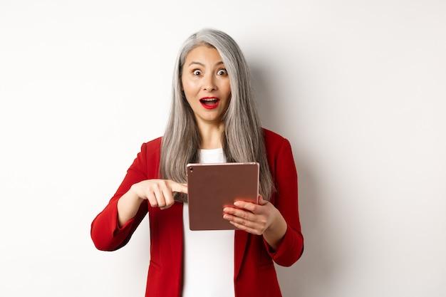 Biznes. zdziwiona kobieta starszy pracodawca, wskazując na ekranie cyfrowego tabletu, wpatrując się w zdumiony aparat, sprawdzając promocję online, białe tło.