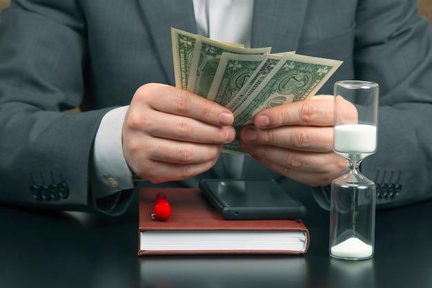 Biznesman w biurze liczy pieniądze na zegary słoneczne