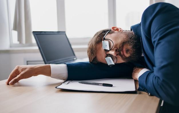 Biznesman w garniturze zasnął w pracy przy stole w biurze. wysokiej jakości zdjęcie