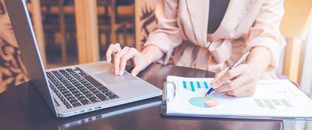 Biznesmen analizując sytuację zapasów. używa pióra i laptopa. na baner internetowy.