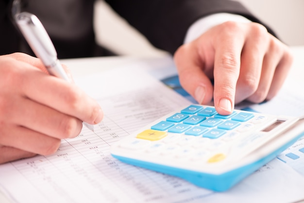 Biznesmen analizujący konto, inwestycję i wykresy z kalkulatorem na biurku