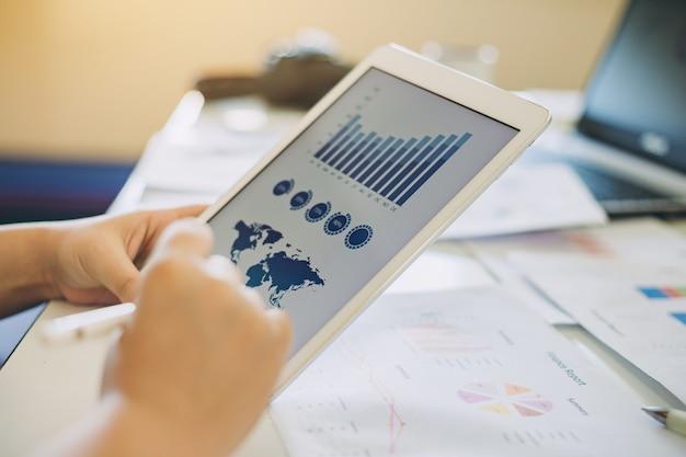 Biznesmen analizujący sprawozdanie finansowe firmy z grafiką dokumentów