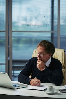 Biznesmen analizuje pieniężną informację w jego biurze