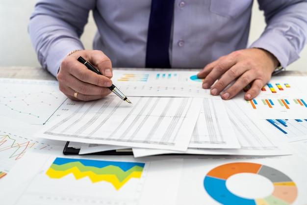 Biznesmen analizuje przychody i wykresy w biurze. analiza biznesowa i koncepcja strategii. biznesmen rozwija projekt biznesowy i analizuje informacje rynkowe, fotosesję z góry
