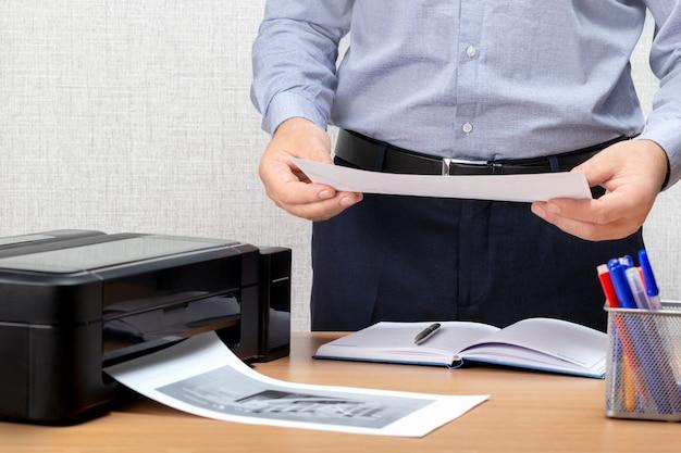 Biznesmen analizuje wykresy inwestycyjne z drukarką. mężczyzna za pomocą drukarki w biurze.