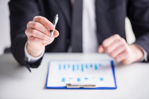 Biznesmen analizuje wykresy w jego biurze.