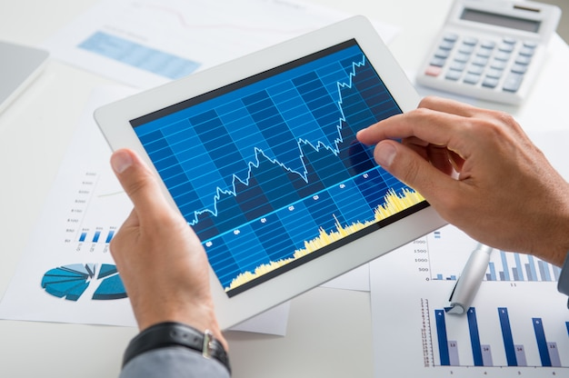 Biznesmen analizuje wzrost z tabletu