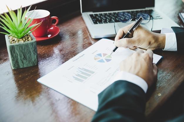 Biznesmen analizy pracy omawianie wykresów i wykresów pokazujących wyniki.