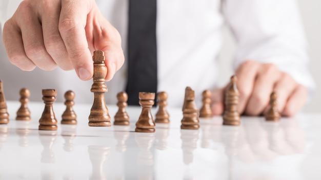 Biznesmen bawić się grę w szachy na bielu stole w zakończeniu w górę widoku jego ręka