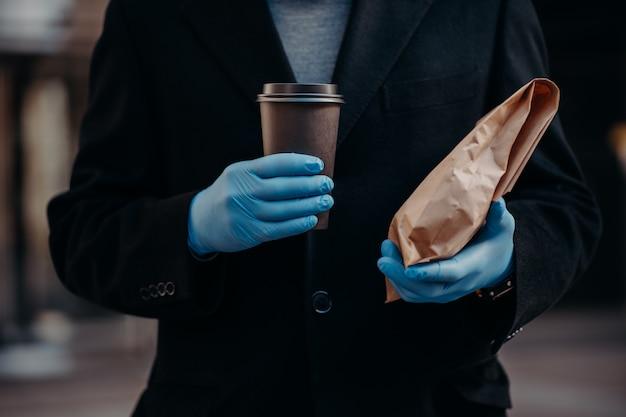 Biznesmen bez twarzy trzyma jedzenie na wynos i jednorazową filiżankę kawy, dla bezpieczeństwa nosi gumowe rękawice medyczne