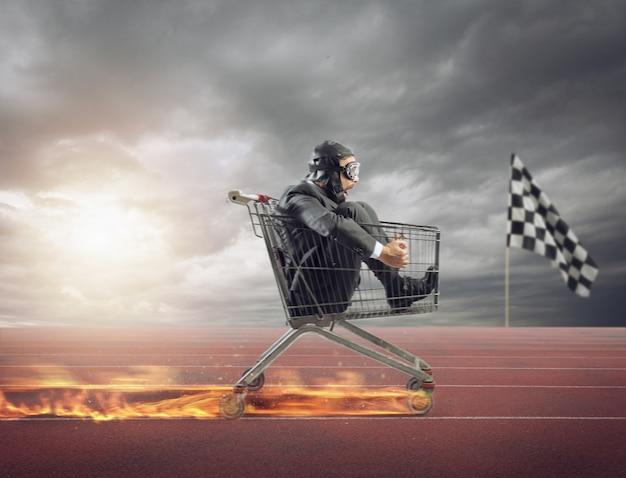 Biznesmen biegnie szybko, prowadząc wóz w ogniu podczas zawodów