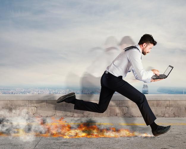 Biznesmen biegnie szybko z laptopem, zostawiając ślady pożaru. szybka koncepcja biznesowa