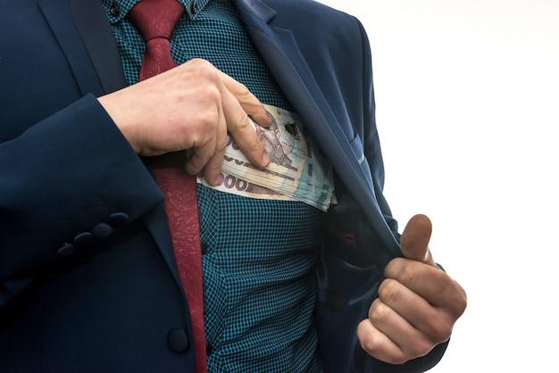 Biznesmen bierze jako łapówkę paczkę ukraińskich pieniędzy i chowa się do kieszeni w kurtce