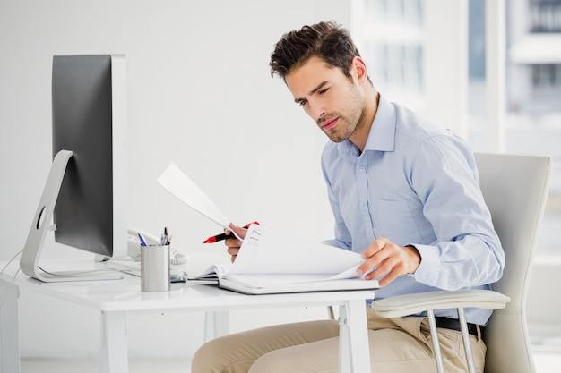 Biznesmen bierze notatki przy jego biurkiem