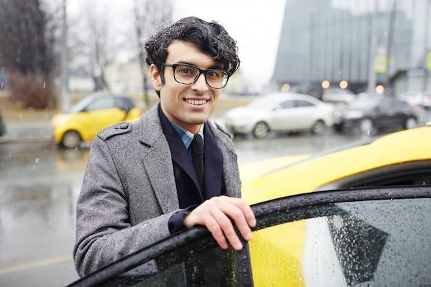 Biznesmen biorąc taksówkę w deszczu