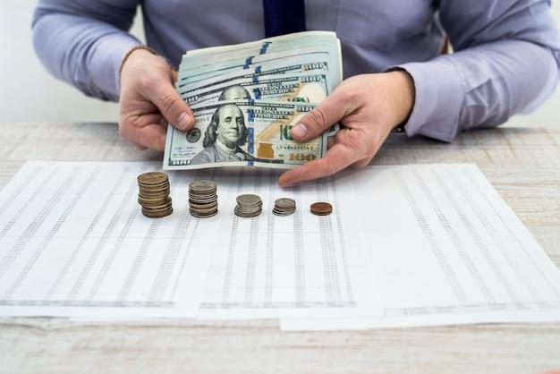 Biznesmen biurowy pracujący i analizujący zyski firmy za pomocą wykresów i dokumentów za pomocą monet. analiza biznesowa i koncepcja strategii