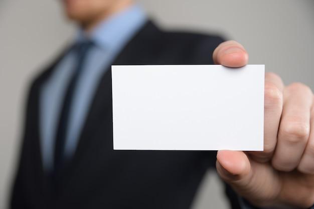 Biznesmen, biznes człowiek trzyma rękę pokazując wizytówkę - bliska strzał na szarym tle. pokaż pustą kartkę papieru. papierowa wizytówka.