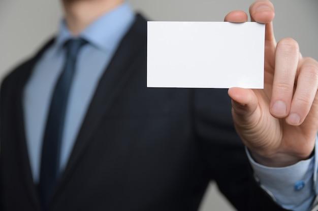 Biznesmen, biznes mans ręka trzymać pokazując wizytówkę z bliska strzał