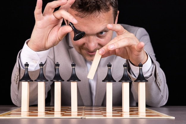 Biznesmen buduje piramidę z szachów i drewnianych klocków