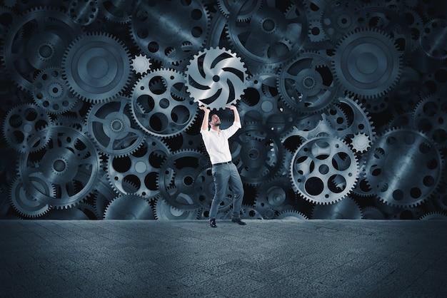 Biznesmen buduje system biznesowy jako mechanizm przekładni i umieszcza brakujące koło zębate