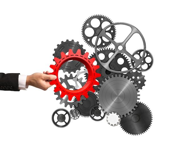 Biznesmen buduje system biznesowy, wprowadzając bieg do mechanizmu