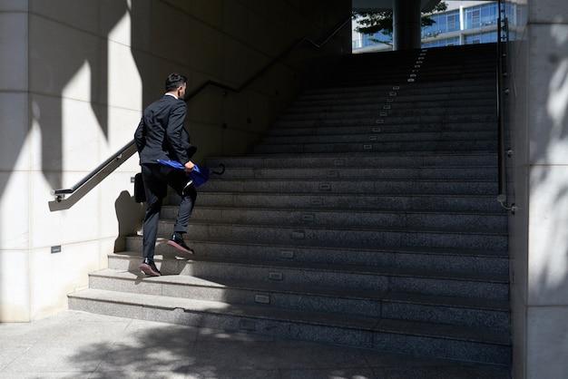 Biznesmen chodzi w górę schody w kierunku biurowego wejścia w kostiumu