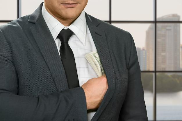 Biznesmen chowa dolary do kurtki.