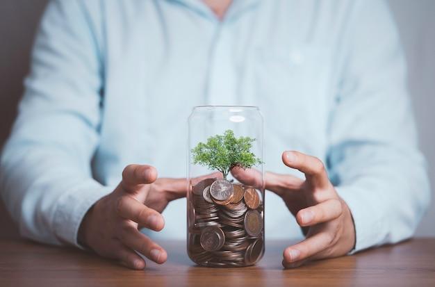 Biznesmen chroni drzewo, które rośnie w środku, oszczędzając słoik monet