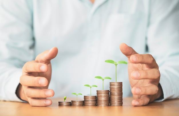 Biznesmen chroni rosnące monety układające się w stos z rośliną wzrostu na stole, aby zapisać koncepcję