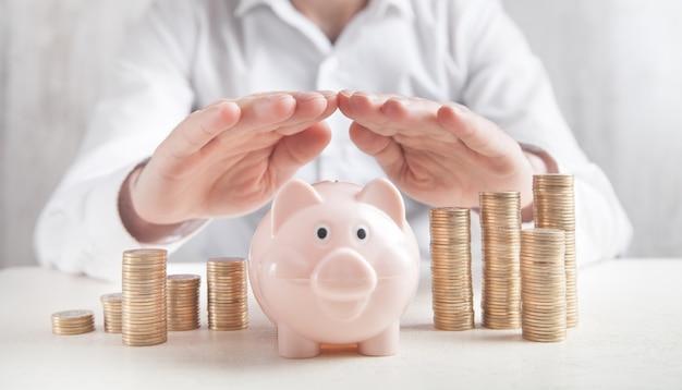 Biznesmen chroni skarbonkę i monety. oszczędzać pieniądze